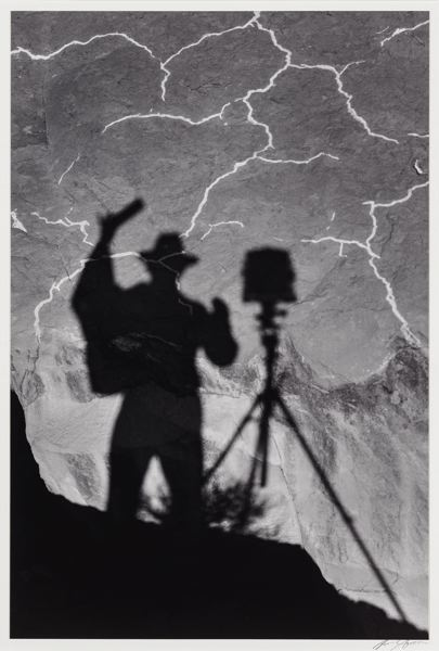 PHOTO: ANSEL ADAMS - Self-Portrait, Monument Valley, Utah, 1958, an early shadow selfie by Ansel Adams taken on a dry lake bed.