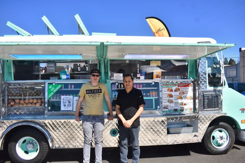 PMG PHOTO: EMILY LINDSTRAND - Richard Schjoth and Juan Luna stand in front of Martha, the vingage food truck they restored to house Kellan's Dogs.
