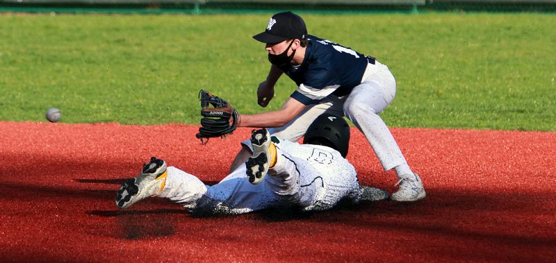 PMG PHOTO: MILES VANCE - Wilsonville junior second baseman Shane Tacia awaits a throw as Putnam's Jason Young slides in to second base during the Wildcats' 15-14 win at Rex Putnam High School on Thursday, April 15.