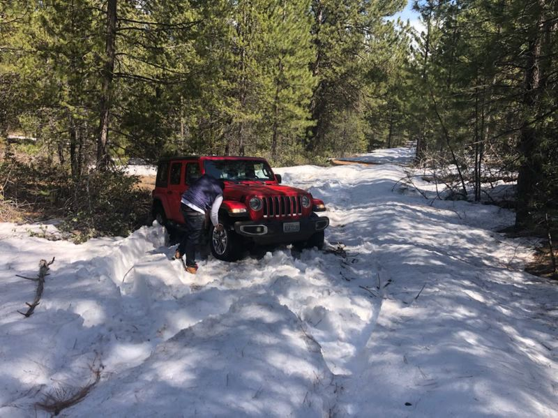 Rented jeep stuck in the snow near bend.