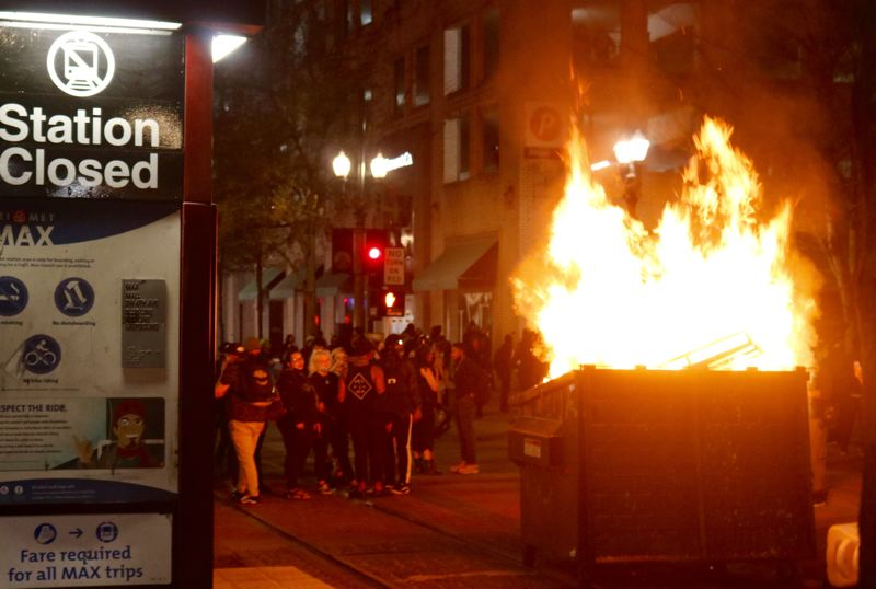PMG PHOTO: ZANE SPARLING - A blazing dumpster fire blocked the MAX tracks along Southwest Yamhill Street near Fourth Avenue in Portland during a downtown riot on Friday, April 16.