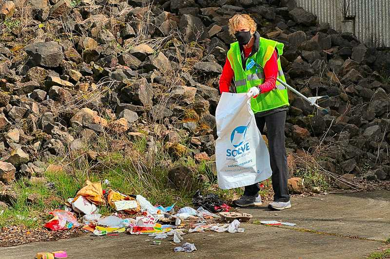 DAVID F. ASHTON - This big bunch of trash was the sort of things volunteers came to remove. Here, Claire Perez gets her bag ready to remove it. She revealed that she came all the way from her home in Sellwood to help out.