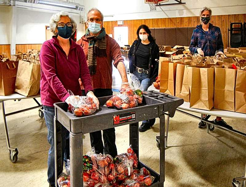 ELIZABETH USSHER GROFF - Woodstock residents Dr. Mary Frazel and Dr. Lowell Chodosh volunteer weekly at a Southeast Portland food pantry that uses innovative food distribution methods. Two Oregon Food Bank volunteers in background are seen helping out.