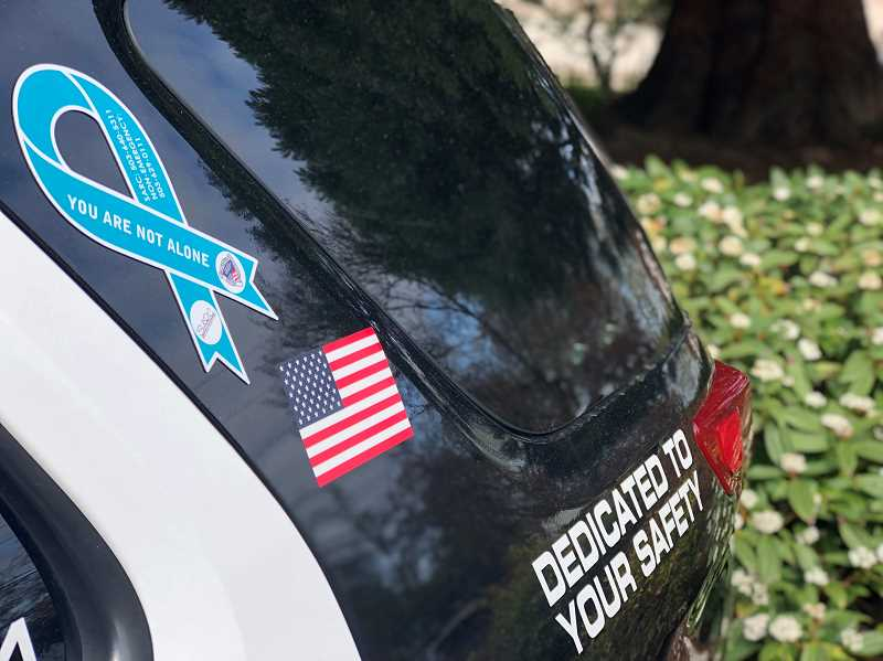 COURTESY PHOTO: BEAVERTON POLICE DEPARTMENT - A marked Beaverton Police Department patrol car with a teal ribbon placed on near a side window. The ribbon was placed to raise awareness during Sexual Assault Awareness Month.