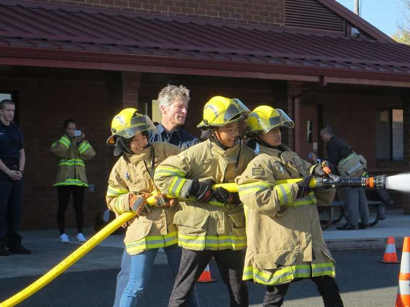 COURTESY PHOTO: FOREST GROVE SISTER CITIES COMMITTEE - Students from Nyuzen, Japan, try out their firefighting skills during a visit to Forest Grove in 2017. Currently, the city is looking at whether to pursue a business relationship with a Latin American country.
