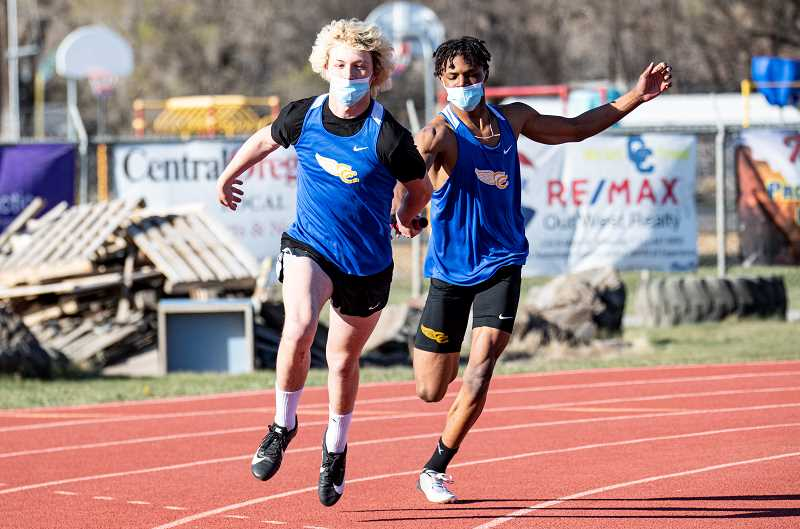LON AUSTIN - Cainen Smith gets the baton from Kyree Willis during the Cowboys' winning 4x100 relay race. Both the Cowboys and Cowgirls had strong meets, winning the Icebreaker at Ward Rhoden Stadium April 15.