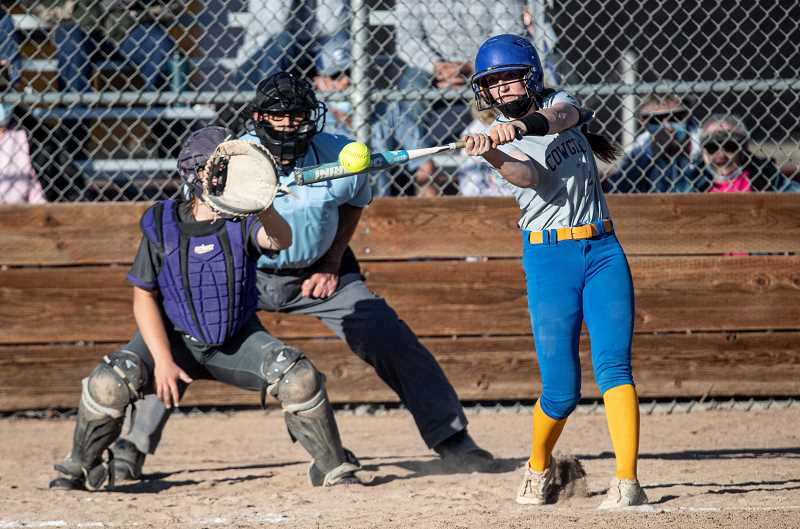 LON AUSTIN - Katelynn Weaver connects for a grand slam home run for the Cowgirls against the defending state champion Ridgeview Ravens. Weaver's monster hit was a highlight for the Cowgirls as they fell twice to Ridgeview.