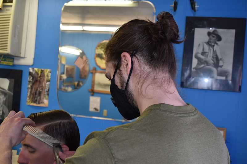 RAMONA MCCALLISTER - Bailey Hamel finishes a haircut on a customer on Friday afternoon. Hamel began working at Monte Gibson's barber shop approximately six months ago.