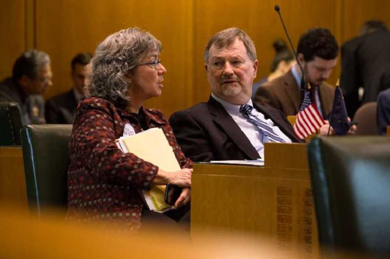 BRADLEY W. PARKS / OPB  - State Rep. Barbara Smith Warner, D-Portland, speaks with Rep. Brad Witt, D-Clatskanie, on the House floor at the Capitol in Salem, Ore., in a 2019 file photo.