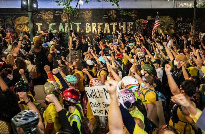 PMG PHOTO: JONATHAN HOUSE - During a 2020 protest, Oregonians march past an 'I Can't Breathe' mural in downtown Portland. Images of George Floyd grace the wall as well.