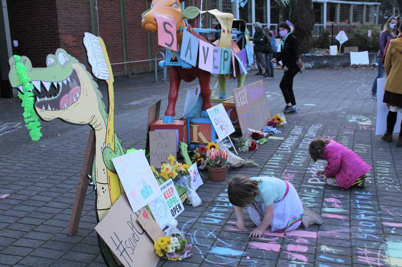 PMG PHOTO: COURTNEY VAUGHN - Quinn and Owynn Ingersoll, 5, use sidewalk chalk to scrawl messages on the ground outside the Portland Childrens Museum during a rally to try to revive the museum.