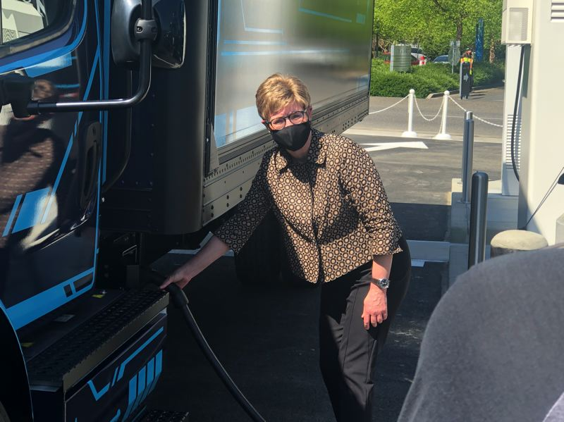 PMG PHOTO: JEFF ZURSCHMEIDE - Maria Pope, President and CEO of PGE, charging a Dailmer electric truck at Electric Isalnd.
