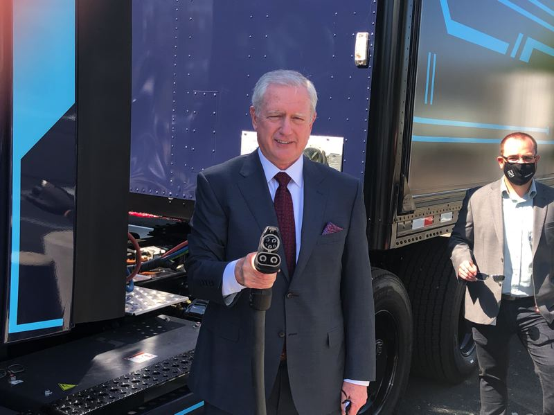 PMG PHOTO: JEFF ZURSCHMEIDE - John O'Leary, President and CEO of Daimler Trucks North America, holds a charging cable and plug at the April 21 opening of Electric Island.