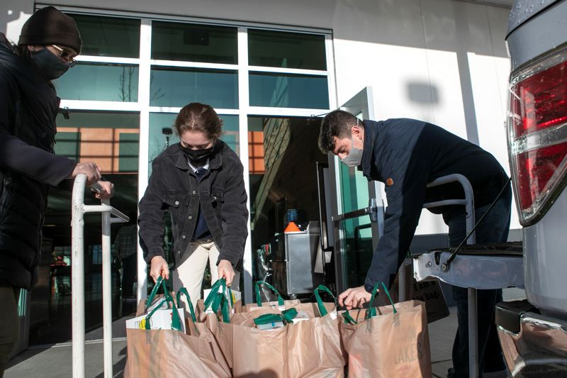 PMG PHOTO: JAIME VALDEZ - Ava Skuvic, left, and Sam Costello, both seniors at Beaverton High School, unload bags of food from vehicles for 120 homeless youth last month.