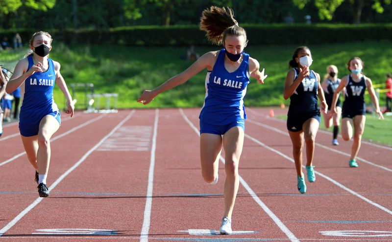 PMG PHOTO: MILES VANCE - La Salle senior Molly Jenne leans across the line to win the 200-meter dash during her team's loss to Wilsonville at Wilsonville High School on Wednesday, April 21.