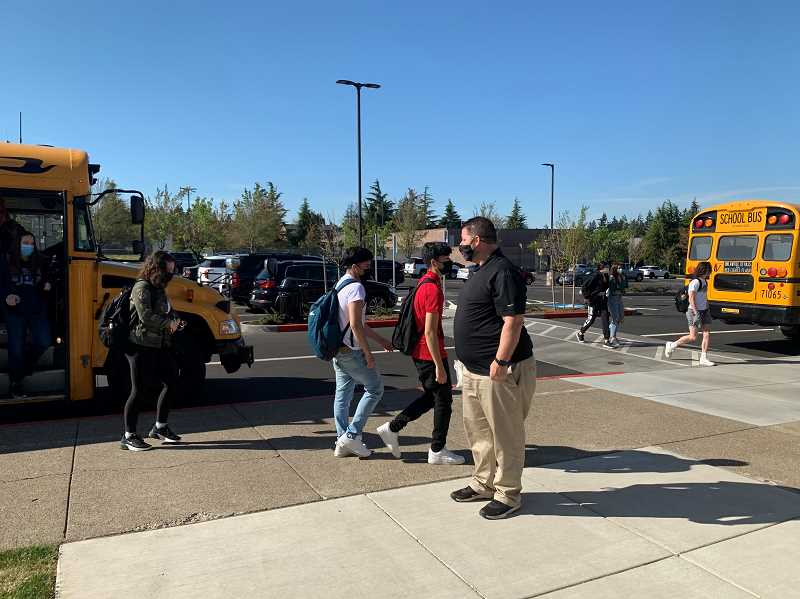 COURTESY PHOTO: TIGARD-TUALATIN SCHOOL DISTRICT - Michael Dellerba greets students getting off the bus during the first week back at Tualatin High School since the pandemic shut down everything last year.