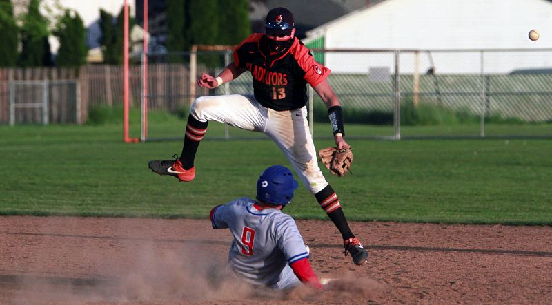 PMG PHOTO: MILES VANCE - Gladstone's Mateo Burgos leaps for a throw while Madras' Dru Boyle slides into second base during the Gladiators' 9-2 win at Gladstone High School on Thursday, April 22.