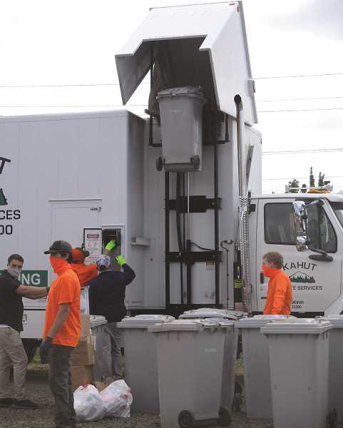 PMG PHOTO: DEBORAH GUINTHER - Another bin goes up to dump its contents in the shredder.