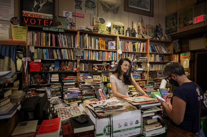 PAMPLIN MEDIA GROUP: JONATHAN HOUSE  - Cameron's Books co-owner Crystal Zingsheim behind the counter at 336 SW 3rd Ave on Friday April 23, 2021. After 83 years in business, the store will close Saturday April 24 at the end of the day, whenever people leave.