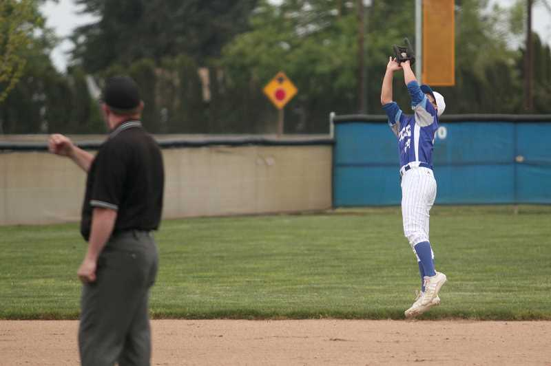 PMG PHOTO: PHIL HAWKINS - Senior shortstop Payson Weise snags an infield fly for the out against Kennedy on Friday. Weise took over at the pitcher's mound in the fourth inning, relieving starter Warren Rose, to close out the Bucks' 14-2 loss to the Trojans.