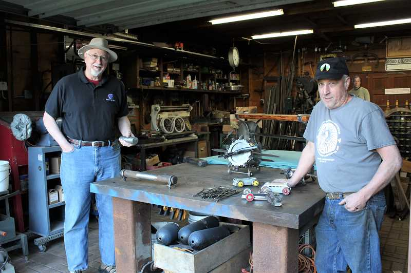PMG PHOTO: COURTNEY VAUGHN - Ted Coonfield (left) and Dan Johnson at Johnsons Laughing Dog Forge studio in Southwest Portland. The two have teamed up to make tables and benches using repurposed items, including pieces of the original OHSU tram car cable.