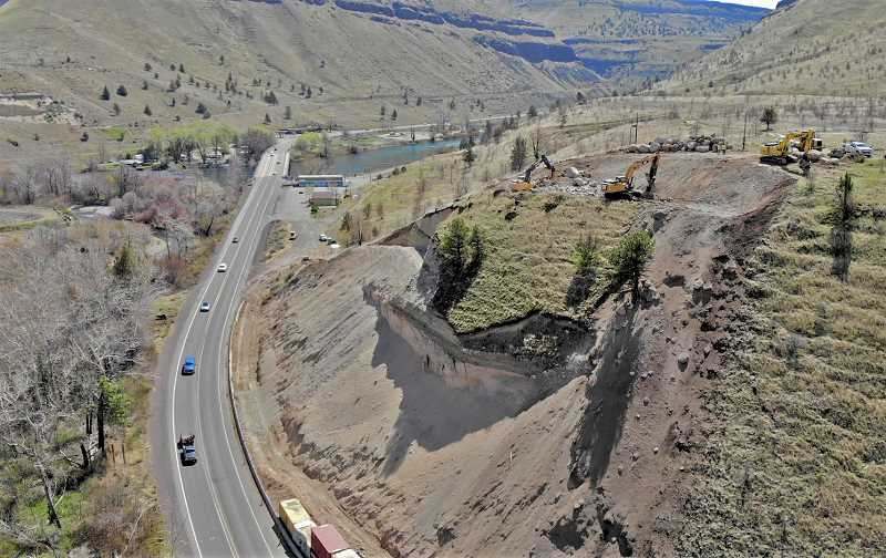 PHOTO COURTESY OF ODOT  - ODOT constructions crews shave off the steep portion of a hillside next to Highway 26 going through Warm Springs to prevent boulders and sloughing debris from falling on the roadway.