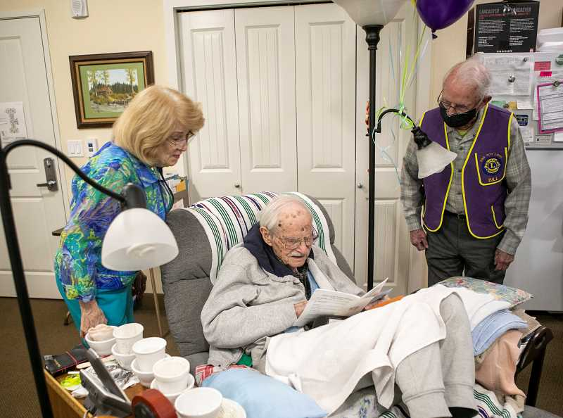 PMG PHOTO: JAIME VALDEZ - Nanette Williams, friend and caretaker of Lionel Domreis, and Bill Gerkin, a member of the King City Lions Club, congratulate Domreis on his 102nd birthday Friday, April 23, at Bonaventure of Tigard, an assisted living and senior living facility.