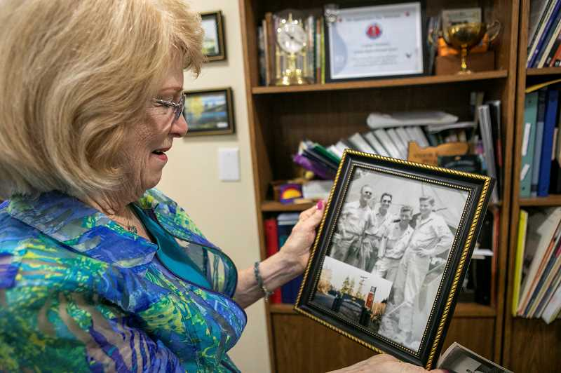 PMG PHOTO: JAIME VALDEZ - Nanette Williams, friend and caretaker of Lionel Domreis, holds a photo of some of Lionel Domreis wartime buddies during a birthday Friday at Bonaventure of Tigard.