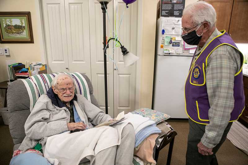 PMG PHOTO: JAIME VALDEZ - Lionel Domreis enjoys a birthday card he received on April 23 as Bill Gerkin, a member of the King City Lions Club, looks on.