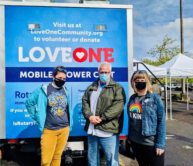 COURTESY PHOTO - Sara Gross Samuelson of Storyline Community; Bill Stewart, community prosecutor with the Clackamas County District Attorney's Office and a Rotarian; and Brandi Johnson, executive director of LoveOne, unveil the cart on April 24.