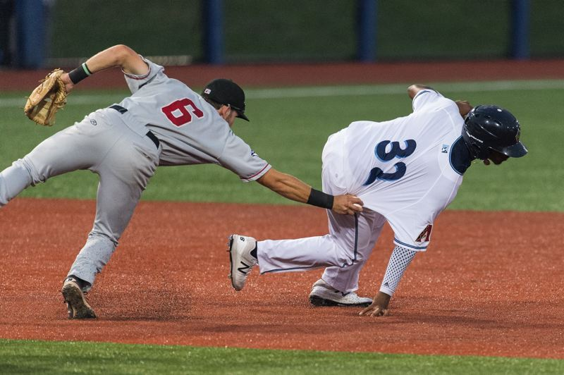 PMG FILE PHOTO - Hillsboro Hops second baseman Tramayne Holmes is tagged out by Vancouver Canadians second baseman Cullen Large during a 2017 baseball game at Ron Tonkin Field. This year, the teams will share the ballpark in Hillsboro due to travel restrictions at the Canadian border.