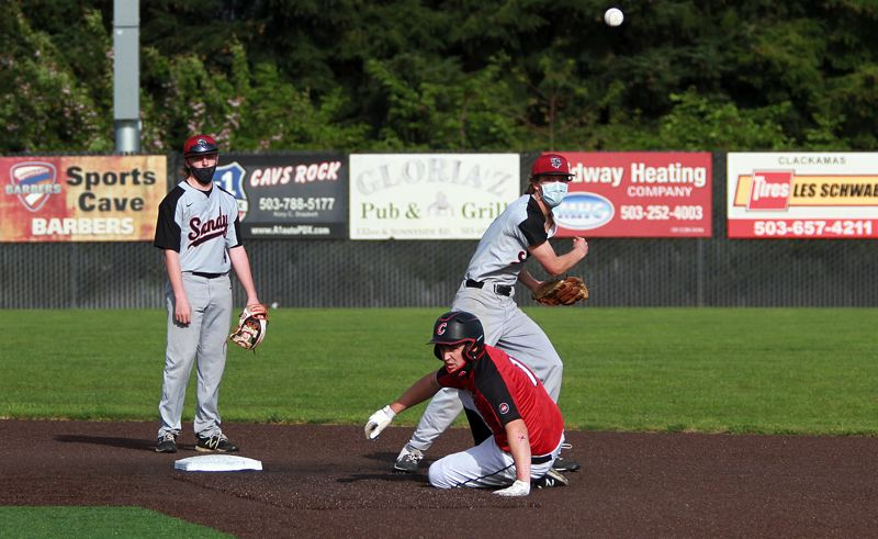 PMG PHOTO: MILES VANCE - Sandy second baseman Bodhi Roach turns a double play after taking a throw from shortstop Danner Hamburg during their team's 5-1 loss to Clackamas at Clackamas High School on Thursday, April 29.