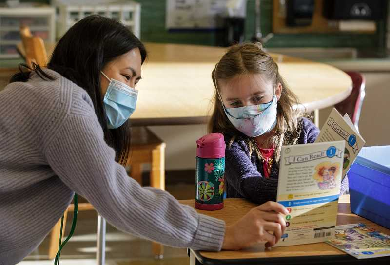 PMG PHOTO: JONATHAN HOUSE - Jason Lee Elementary School teacher Alisa Vuong helps Anna Clutter with a reading assignment during the first day back at school for hybrid learning. Despite distancing protocols and mask mandates in schools, Oregon is still seeing infections among students and staff.