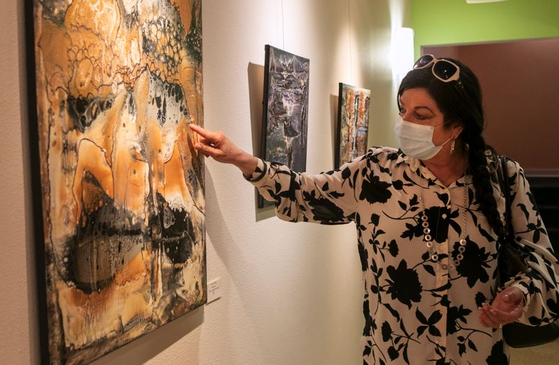 PMG PHOTO: JAIME VALDEZ - Carole Zenny points to texture in one of her paintings on display at the Glenn & Viola Walters Cultural Arts Center.