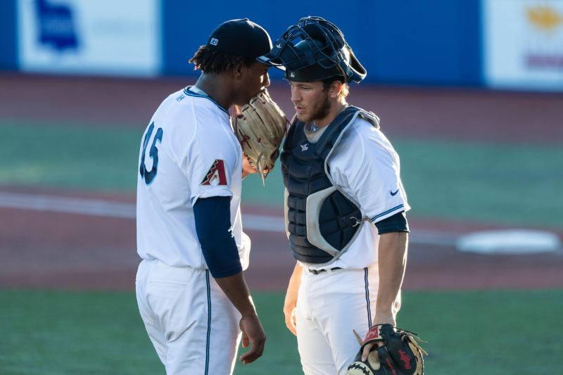 PMG FILE PHOTO - Hillsboro Hops pitcher Luis Frias and catcher Nick Dalesandro meet for a discussion during a 2019 game. Frias and Dalesandro are both back with the Hops in 2021.