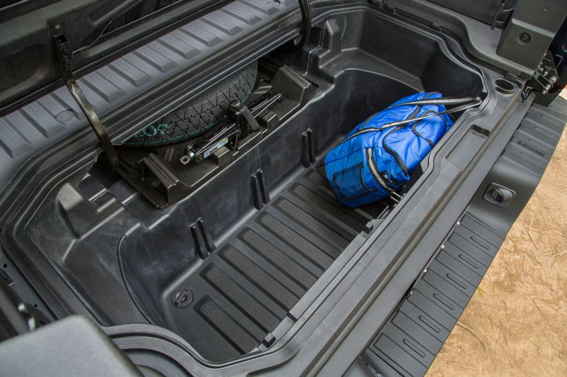 HONDA AMERICA MOTOR CO. - The 2021 Honda Ridgeline features a unique dual action tailgate that folds down or swings to the side, and a storage space with a drain plug under the bed next tothe spare tire.