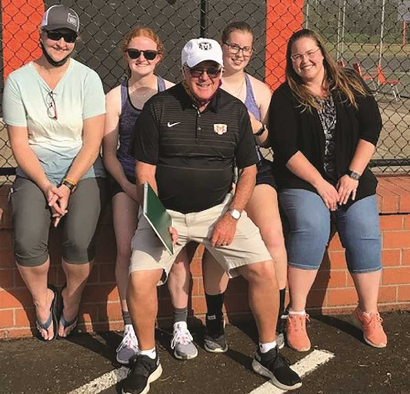 COURTESY PHOTO: MIKE CLARKE - Head coach Mike Clarke (front) and a couple generations of players he's coached. Current undefeated doubles team, Hannah Nelzen (second from left) and Alyssa Beatty (second from right) are flanked by their moms - Lauree Nelzen (left) and Jennifer Beatty (right) - who also played for Clarke years before. Nelzen and Beatty will be the No. 1 seed in doubles when the conference tournament commences on May 10 in Madras.