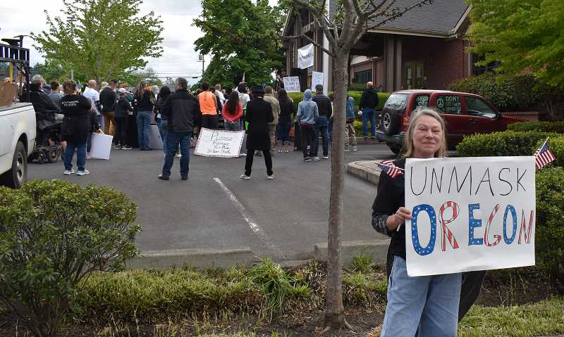 PMG PHOTO: RAYMOND RENDLEMAN - Lorraine Burger of Scappose joined a May 1 protest in Oregon City's city-hall parking lot.