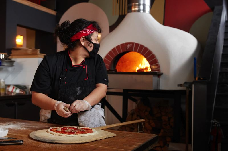 COURTESY PHOTO: URBAN DECANTER - A cook at Urban Decanter tops a pizza to be placed in the wine bar's wood-fired oven.