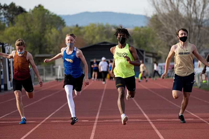 LON AUSTIN - Alex Smith, left, and Zach Guthrie  at the end of the 200. Guthrie won the race and Smith was second. Guthrie also won the 100 and long jump to help Crook County's boys dominate Hood River and Redmond.