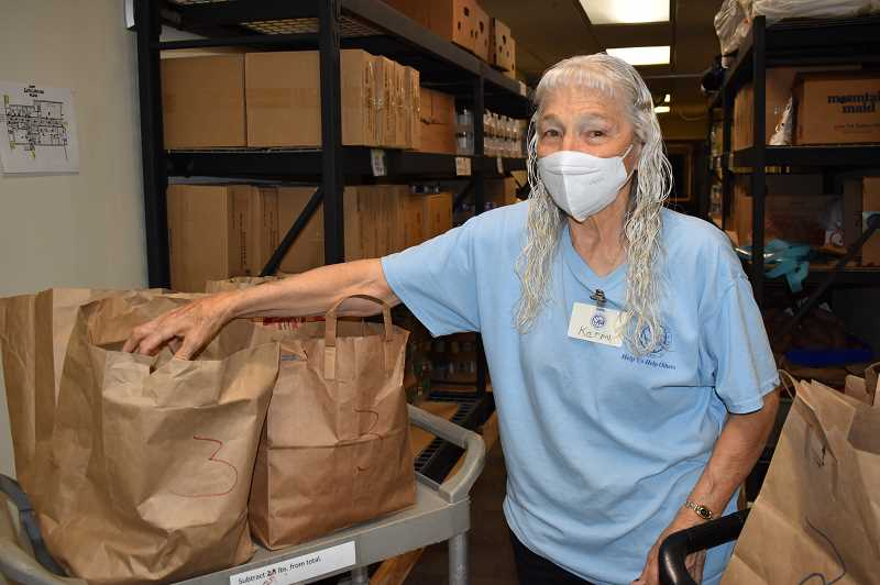 RAMONA MCCALLISTER - Karin Davis, who has volunteered for St. Vincent de Paul in Prineville for more than 16 years, stands by a number of bags that will go out to patrons later in the day.