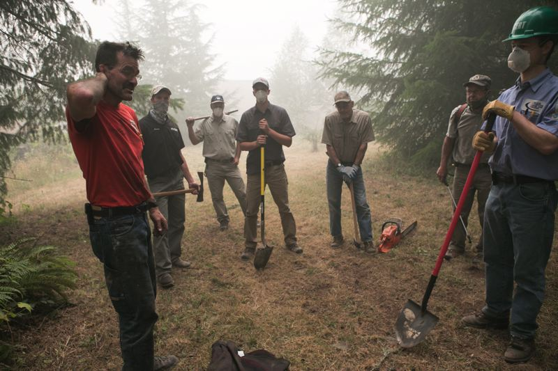 PMG PHOTO: JAIME VALDEZ - A group of neighbors help Paul Clement, pictured in the red shirt, remove plants and trees from hotspots left over from the Riverside fire from his property on Fall Creek Road last year.