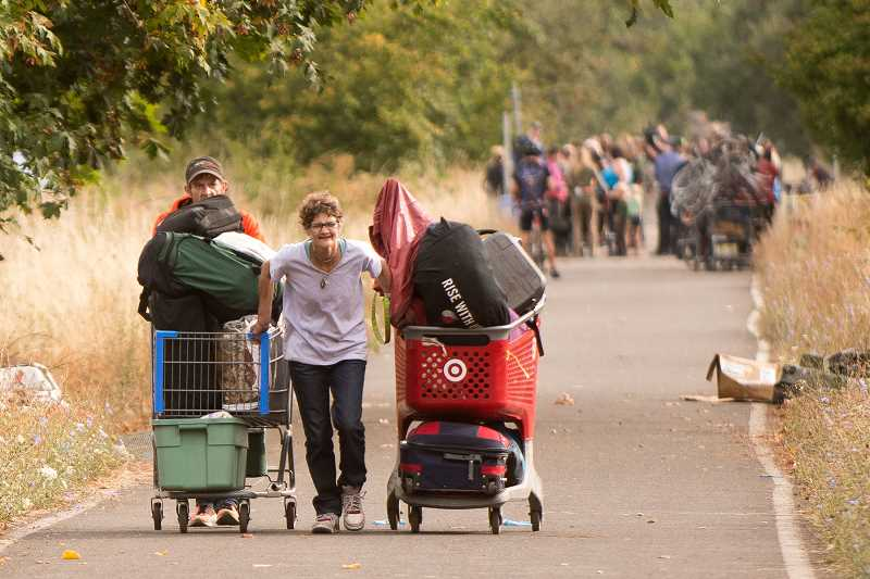 PMG PHOTO: JOSH KULLA - A homeless couple moves their belongings along the Springwater Corridor Trail while other campers gather in the background.