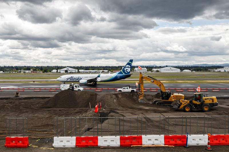 PAMPLIN MEDIA GROUP: JONATHAN HOUSE - Concourse B is being built near the south runway, and next to a live taxi way for planes, some of whose asphalt is currently being resurfaced by other work crews.
