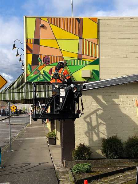 COURTESY PHOTO: CITY OF TIGARD - A worker installs a mural panel alongside Main Street Stamp and Stationery in April.