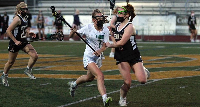 PMG PHOTO: MILES VANCE - West Linn's Eva Murray races upfield while defended by Clackamas-Oregon City's Mairin Kelly during the Lions' 13-6 win at West Linn High School on Thursday, May 6.