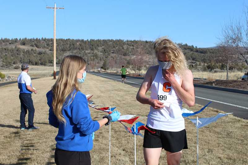 TONY AHERN  - Jacob Horat, a Culver distance runner, adjusts his mask after finishing first in a March cross country race in Madras.