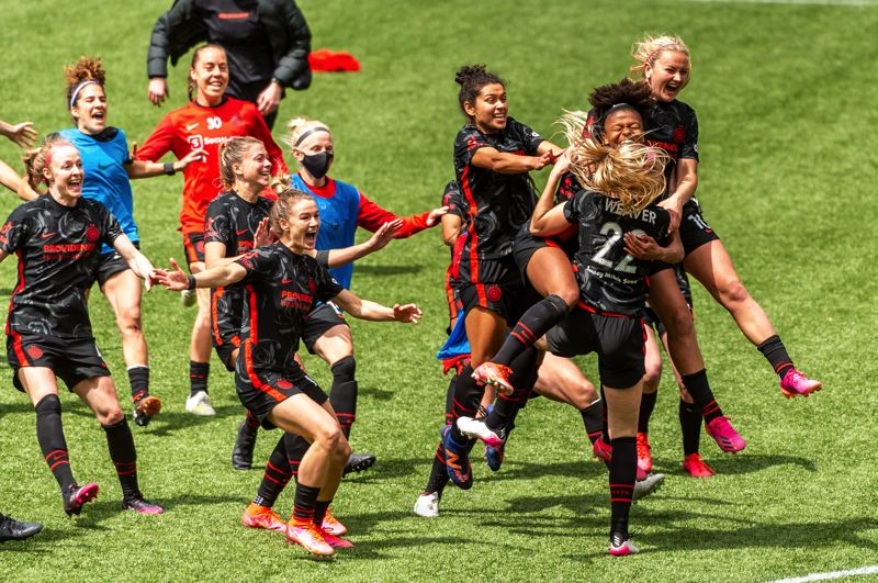 PMG PHOTO: DIEGO G. DIAZ - Portland Thorns players rush to celebrate with Morgan Weaver after her penalty kick sealed a victory in Saturday's championship match of the NWSL Challenge Cup tournament at Providence Park.