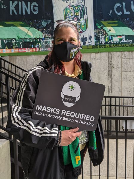 PAMPLIN MEDIA GROUP: JOSEPH GALLIVAN - Nicola Whitchurch, AKA Cola, in her usual spot in the corner of the North End, encouraging fans to keep their masks on between swigs and bites.