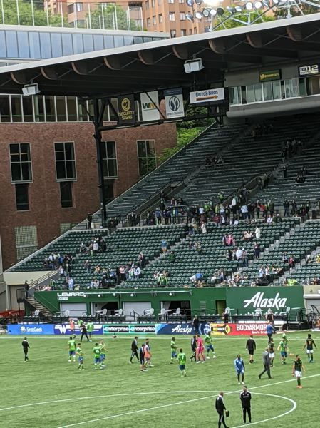 PAMPLIN MEDIA GROUP: JOSEPH GALLIVAN - May 9, 2021, Providence Park: After the final whistle, victorious Seattle Sounders players go to the corner of the stadium where their fans usually congregate.